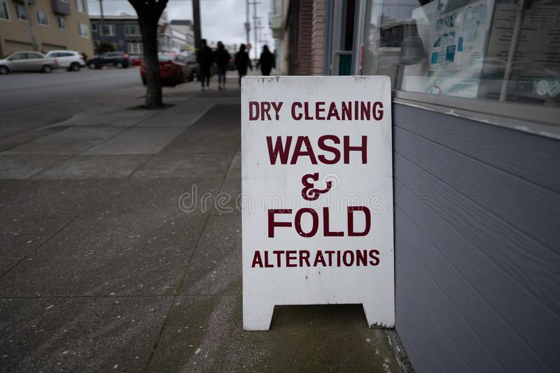 Dry cleaning wash and fold alterations signboard outside of store on sidewalk. Dry cleaning wash and fold alterations signboard outside of store on a sidewalk stock photography