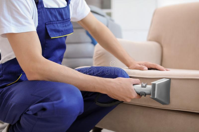 Dry cleaning worker removing dirt from sofa stock images