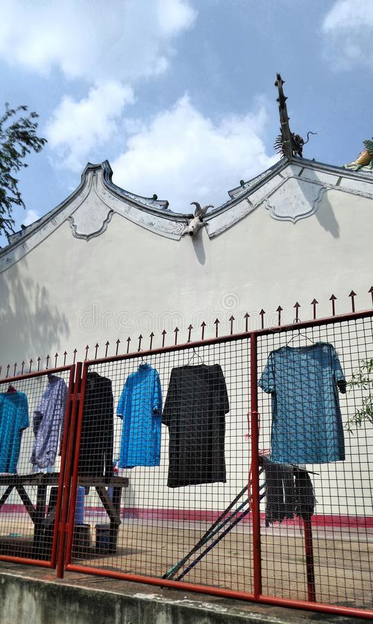 Dry clothes in wire fence next to a Chinese Shrine in the market stock photo