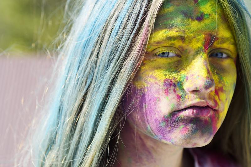 Dry color on face. Colorful holi on painted hair and face. Girls with colorful hair and face enjoing in the moment. Dry. Color concept. Happy life in teenager royalty free stock photo