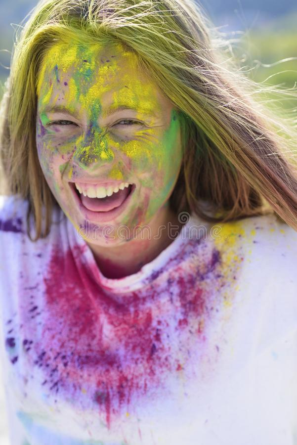 Dry color on face. holi. colorful neon paint makeup. Crazy hipster girl. Summer weather. Happy youth party. Optimist. Spring vibes. child with creative body royalty free stock image