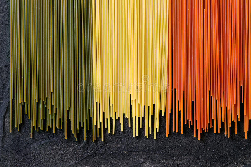 Dry colorful pasta spaghetti. As italian flag over black textured background. Top view stock photography