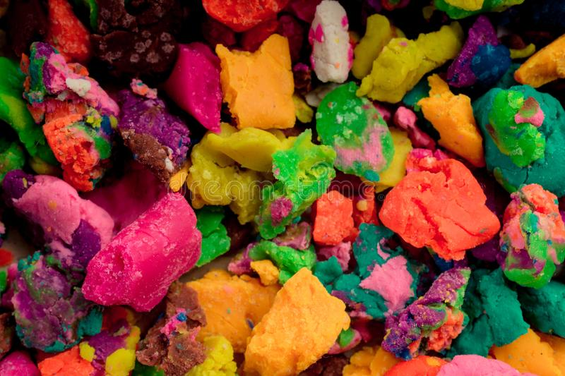 Dry colorful play dough in pieces. Dry colorful play dough in smal pieces stock photos