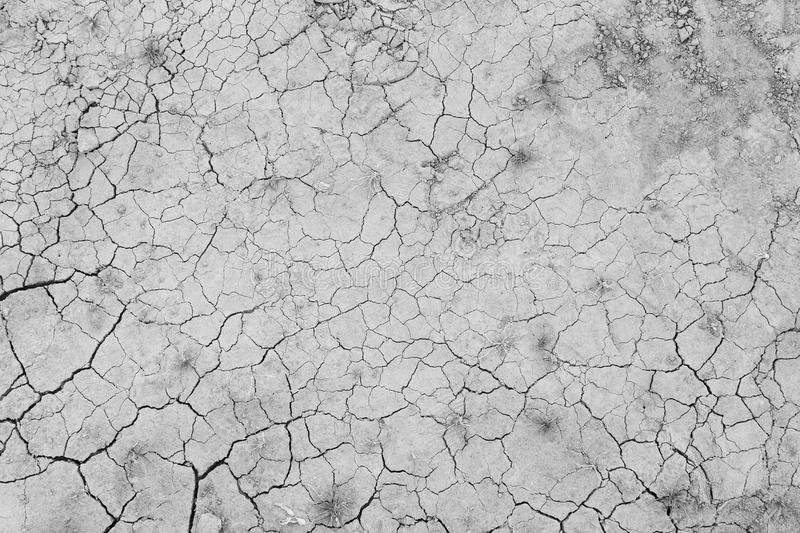 Dry and cracked ground from above. Dry and cracked soil ground during drought, viewed from above in black and white royalty free stock image