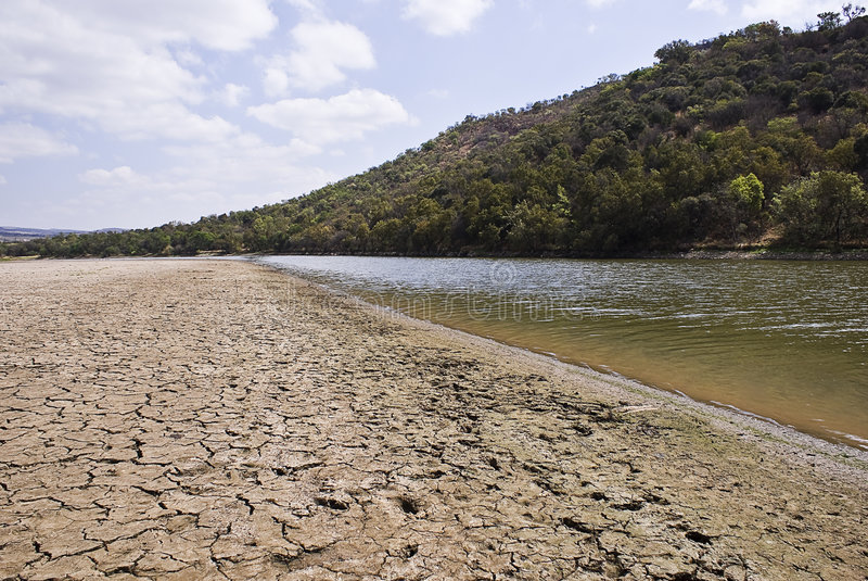 Dry Cracked Riverbed & River. The water level in this river is low. Dried up banks of the Crocodile river. The Crocodile river is one of the major rivers that royalty free stock photos