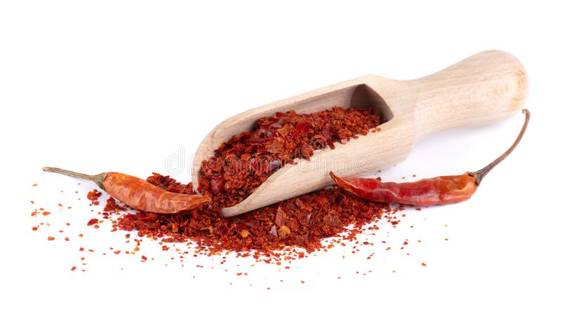Dry and crushed chili pepper flakes isolated on white background. Red chili peppers in a wooden spoon. royalty free stock photography