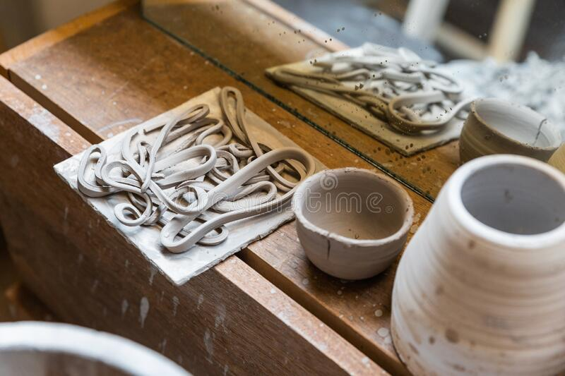Dry cut pieces of ceramic on a concrete plate with incomplete ceramic cups in front of a mirror on wooden sideboard. Ceramic handcraft workshop stock images