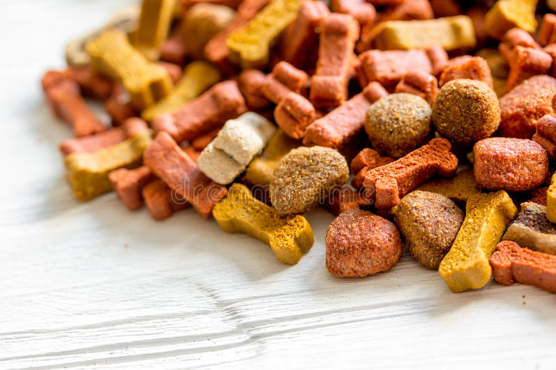 Dry dog food in bulk on wooden background close up.  royalty free stock image