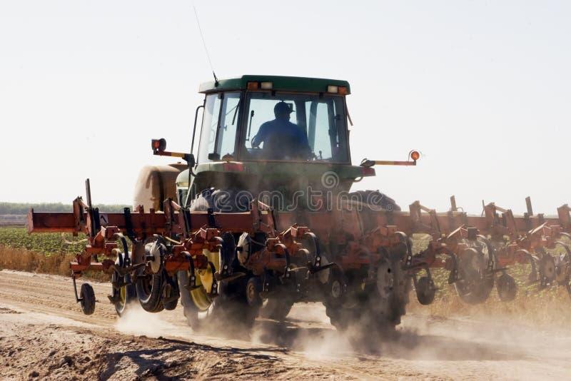 Dry dusty Arizona desert farming. Farm tractor drives along dry dusty desert farm corn field royalty free stock images