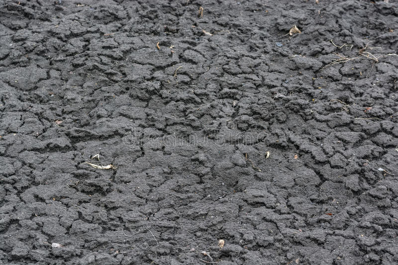 Dry fall ground with cracks. Close up of dry dark autumn ground with some cracks in it stock image