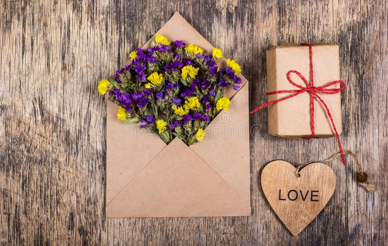Dry field flowers in a paper envelope. Romantic letter. A wooden heart. royalty free stock photos