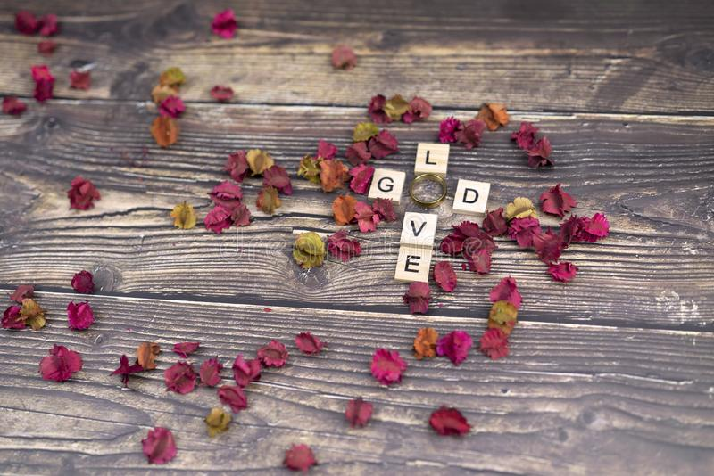 Dry flower and god and love spelling for background stock photography