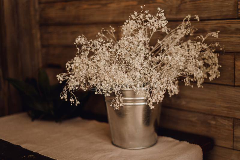 Dry Flower Metal Bucket Vase Decor on Wooden Shelf. Dried Mimosa Blossom for Chalet Design Home Interior. White Floral Decoration in Rural Brown Room stock images