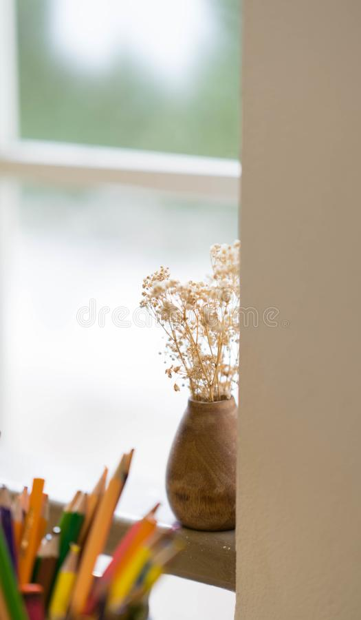 Dry flowers in baked clayy vase near window selective focus. Dry flowers in baked clayy vase near window day time view stock photos