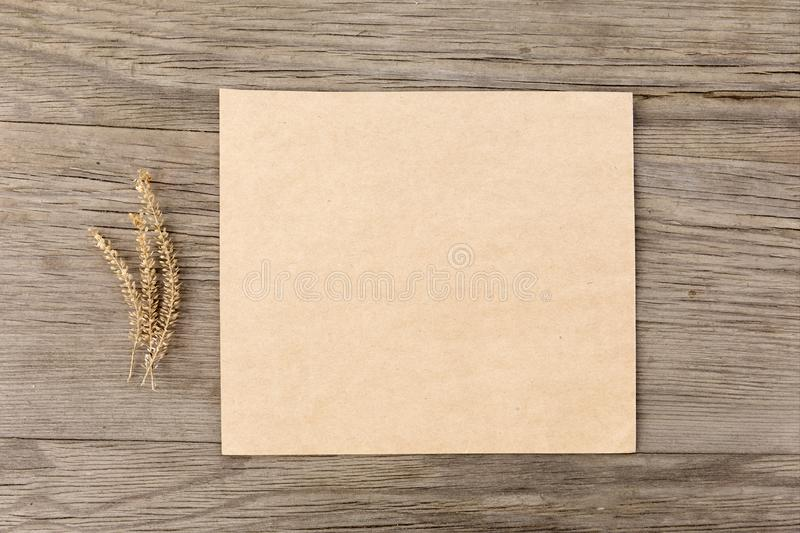Dry flowers with craft blank paper on old grunge wooden background. Top view. Minimalistic mockup. stock photo