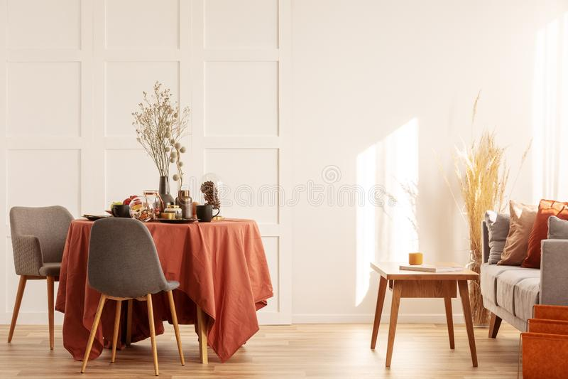 Flowers in vase on dining table covered with dark orange tablecloth royalty free stock image