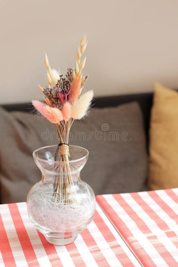 Dry flowers in a vase on table of cafe. Italian tablecloth on the table, soft pillows as a background royalty free stock photos