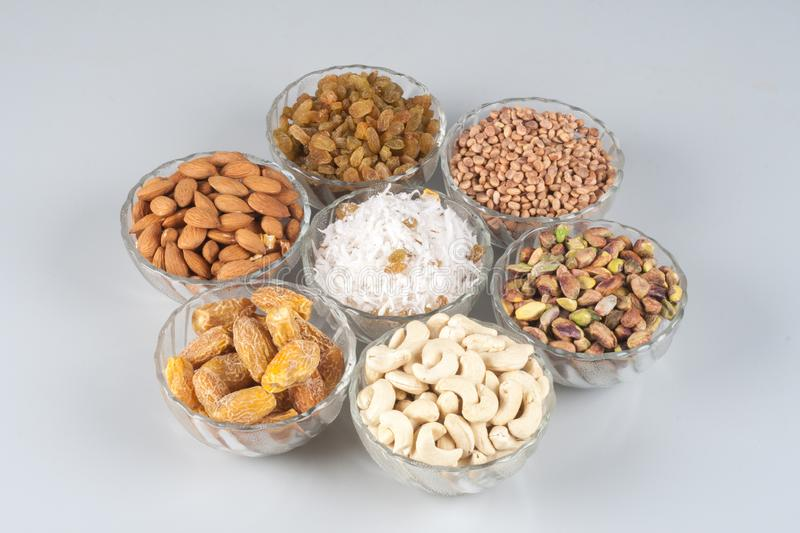 Dry fruits. In glass bowls with background image, isolated image of dry-fruits, almond, pistachio,raisins, graded coconut,dry-dates and Cjironji or charoli stock photography