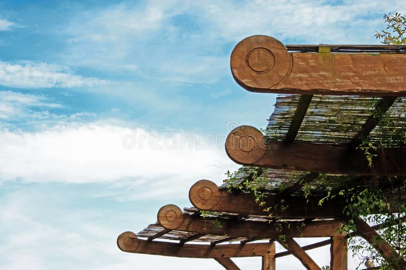 Dry grass hay roof with wooden design decorative elements on blue sky with light fluffy white clouds background stock photography
