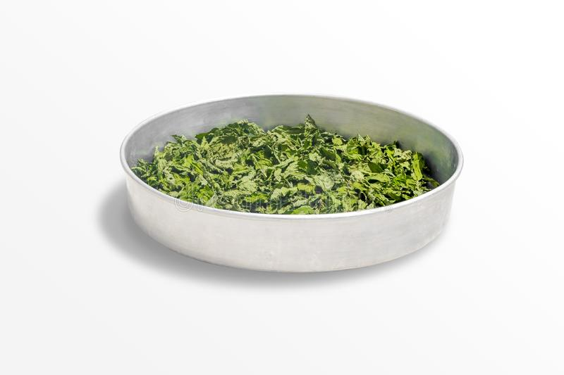 Dry healing mint leaves on a metal bowl isolated on white background. Seasoning Peppermint on a round tray stock images