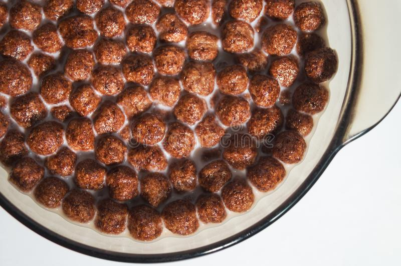 Dry healthy chocolate breakfasts in the form of balls in a plate of milk. Flakes of wheat and corn. royalty free stock image