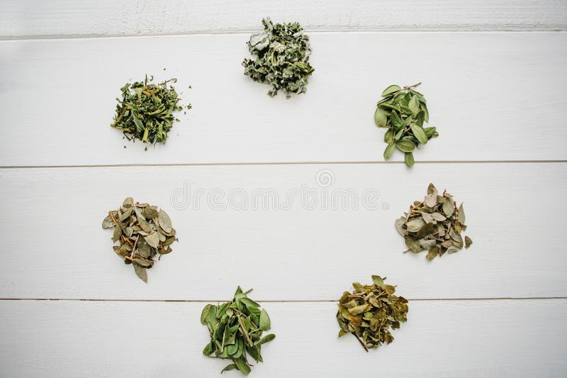 Dry herbs of cowberry, blueberry, raspberry, melissa. Various dry useful herbs for tea preparation lie on a white wooden. Dry herbs of cowberry, blueberry royalty free stock photos