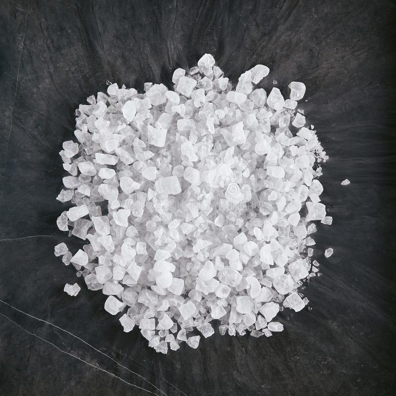 Dry Ice Crystals or Solid Carbon Dioxide on Natural Black Stone Background. Round heap of various dry ice crystals on natural black stone background top view royalty free stock photo