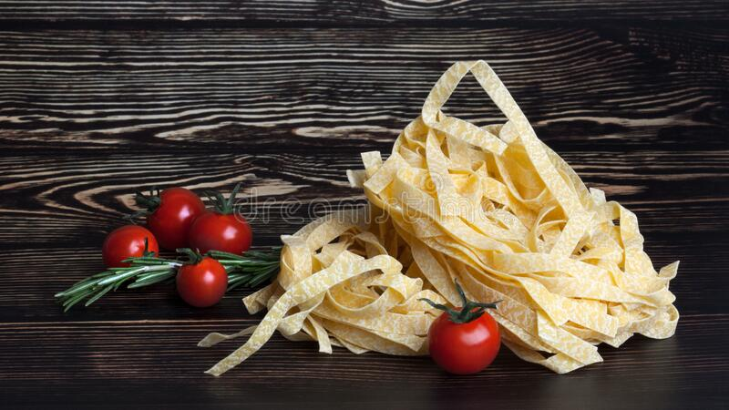 Dry Italian pasta fettuccini with tomatoes and rosemary. On dark wooden background. With copy space stock photos