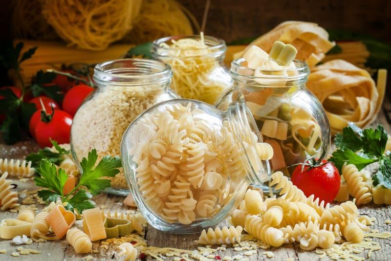 Dry Italian pasta spiraline in glass jars, selective focus stock photography