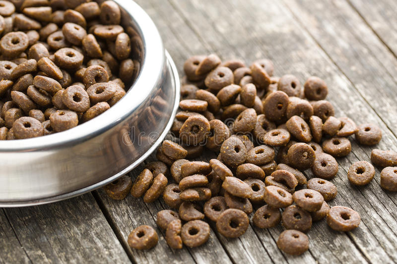 Dry kibble dog food. Dry kibble dog food in bowl on old wooden table stock photos