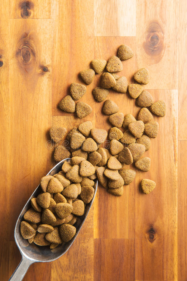 Dry kibble dog food in scoop. Dry kibble dog food in metal scoop on wooden table. Top view royalty free stock photos