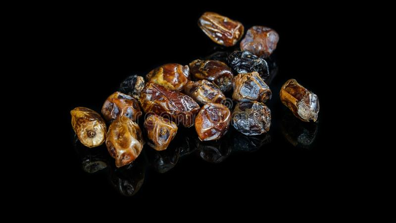 Bunch of dry kurma dates or palm  in black with reflection below it stock photo