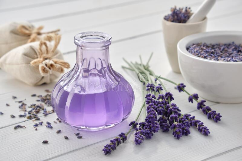 Dry lavender flowers, bottle of essential oil or flavored water, sachet and mortar on white table stock image