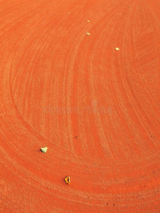 Dry leaf an tennis court. Dry light red crushed bricks surface on outdoor tennis ground. End of season. stock image
