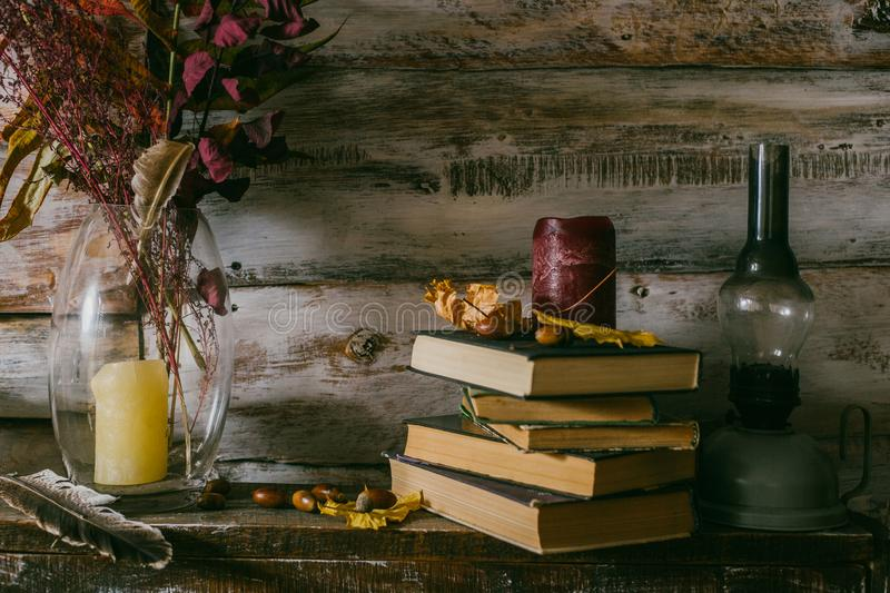 Dry leaves in a vase. vintage interior. books, candle and oli la royalty free stock photo