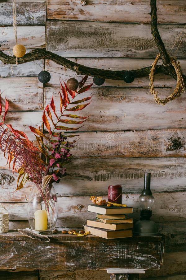 Dry leaves in a vase. vintage interior. books, candle and oli la royalty free stock photography
