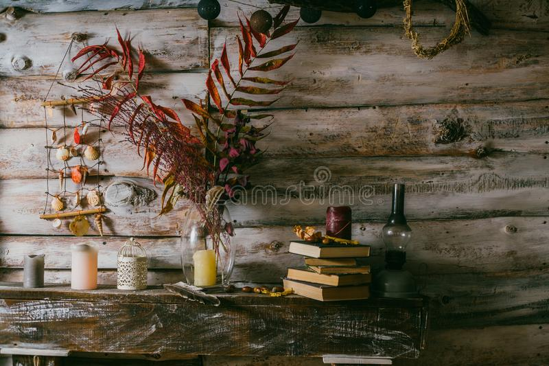 Dry leaves in a vase. vintage interior. books, candle and oli la stock photos
