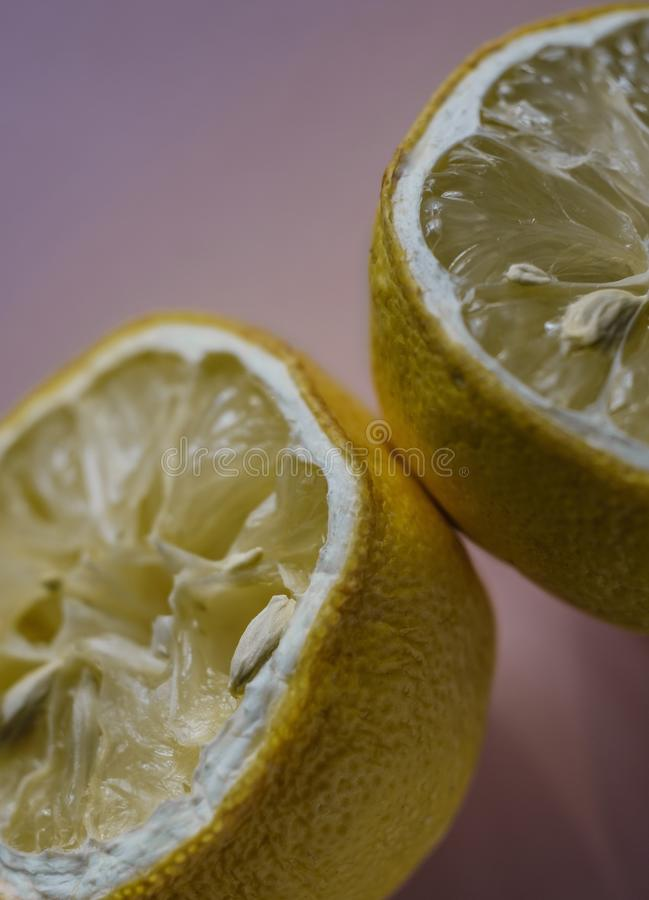 Dry lemon halves on pale pink background stock photo