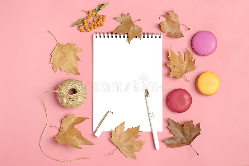 Dry maple leaves, macaroons and white notepad on pink background Autumn concept To do list Mock up Top view Flat lay. Copy space stock photo