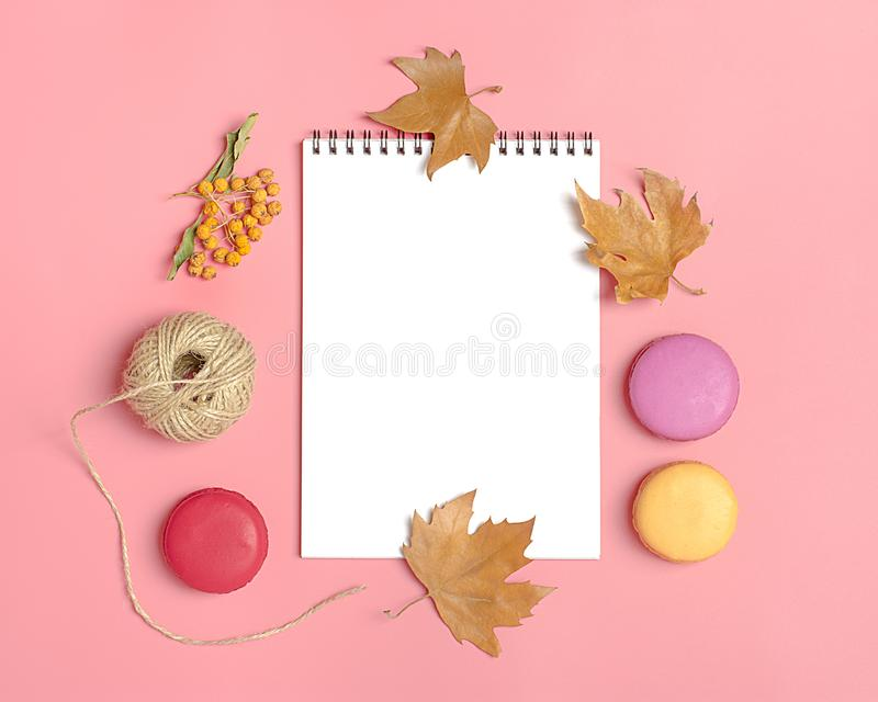 Dry maple leaves, macaroons and white notepad on pink background Autumn concept To do list Mock up Top view Flat lay. Copy space stock photos