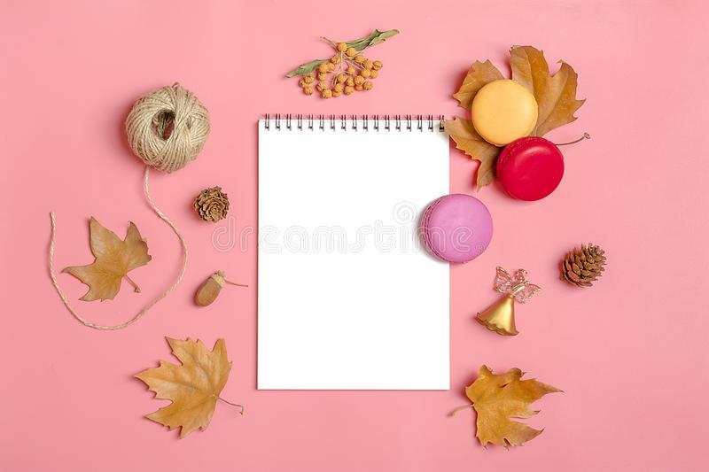 Dry maple leaves, macaroons and white notepad on pink millennial background Autumn concept To do list Mock up Top view Flat lay. Copy space royalty free stock images