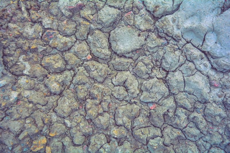 Dry mud ground, crack texture, granite gravel. Dry dirty soil. Cracks on clay. Dry mud ground with crack texture and granite gravel. Dry dirty soil on summer royalty free stock photos