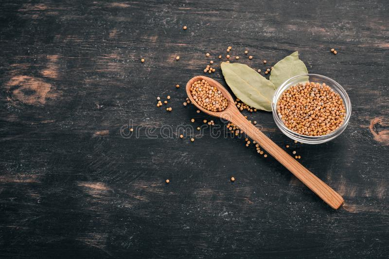 Dry Mustard Grain. Spices. On a wooden background. Top view. Copy space for your text stock image
