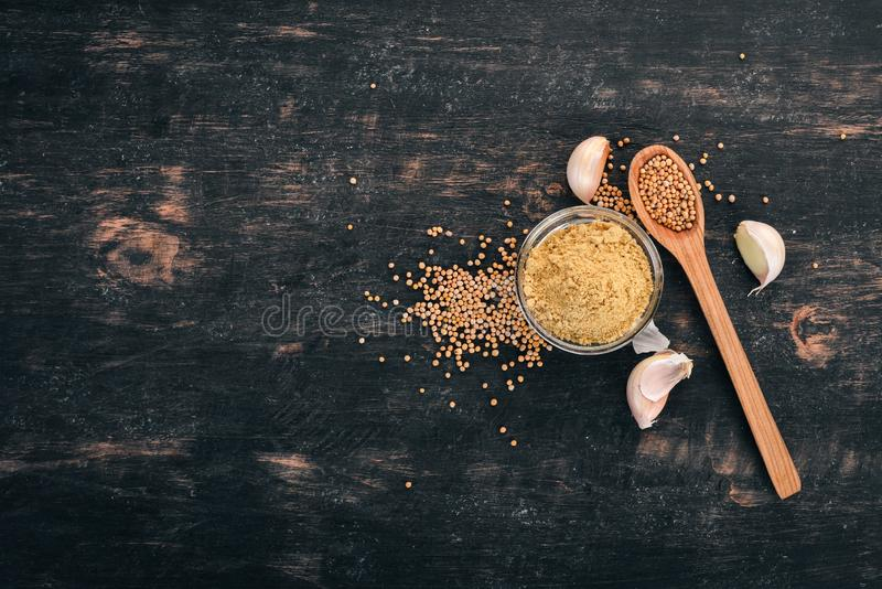 Dry Mustard Grain. Spices. On a wooden background. Top view. Copy space for your text stock photography