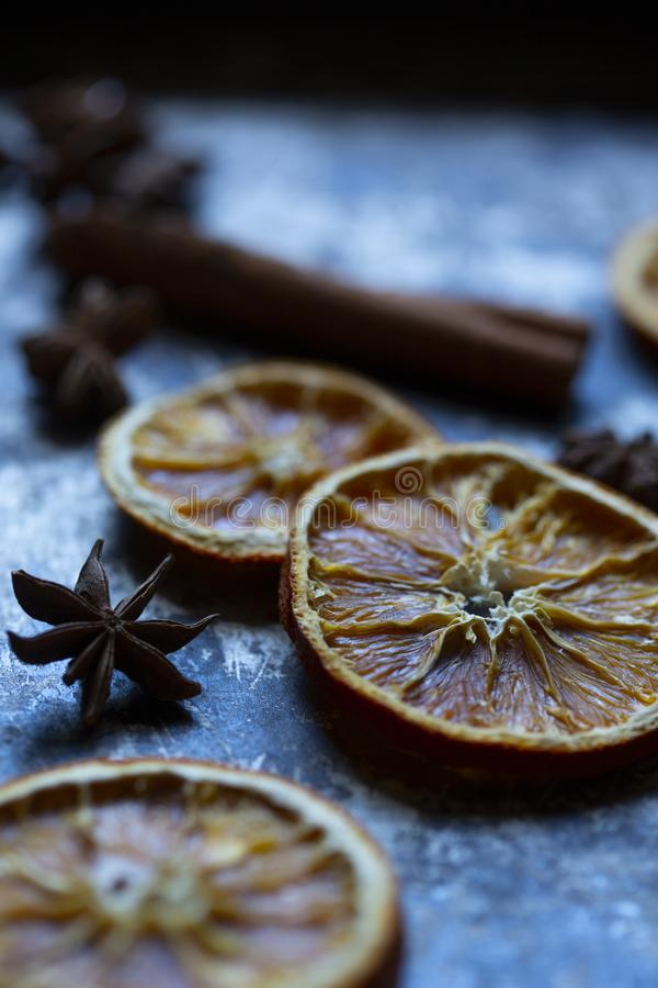 Dry orange, cinnamon stick and anise on old  grey and black baking tray. stock photo