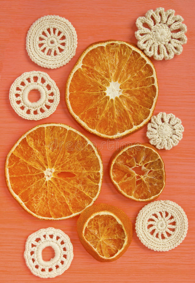 Dry oranges and white vintage elements of Irish crochet. Doilies, circle coasters, creative craft work stock photography
