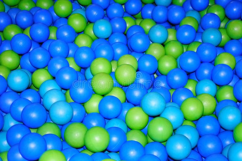 Dry paddling pool with green and blue plastic spheres. Blue cheerful background royalty free stock photography