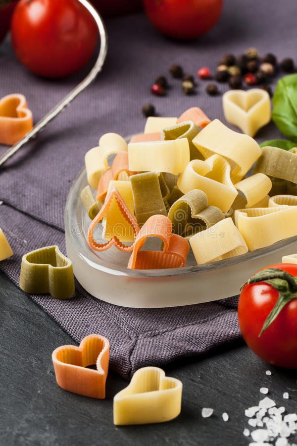 Dry pasta as hearts. Close up of dry colorful pasta as heart shape with fresh tomatoes and basil served on dark gray background royalty free stock image