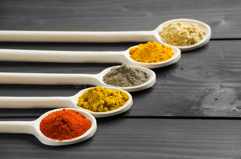 Dry powder spices in wooden mixing spoons at the table royalty free stock photography