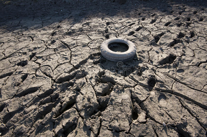 Dry river bed. With old tire - concept image of global warming an ecology stock image